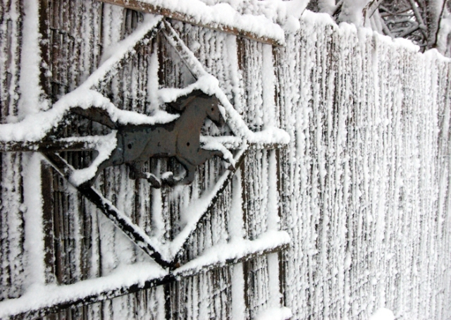 Horse motif on snow covered fence